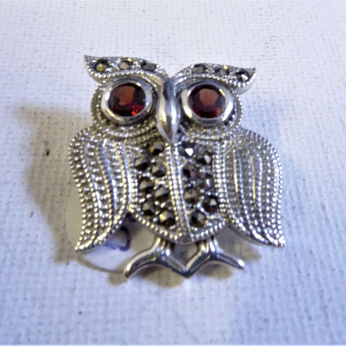 Silver and marcasite owl brooch with garnet eyes, available with amethyst and blue topaz eyes.